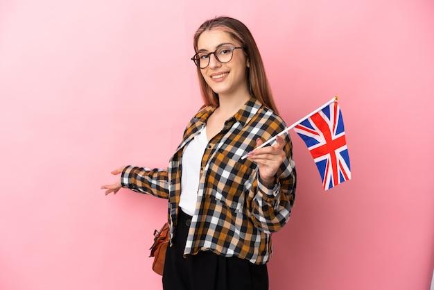 ピンクの壁に隔離されたイギリスの旗を持っている若いヒスパニック系の女性が来て招待するために手を横に伸ばしています