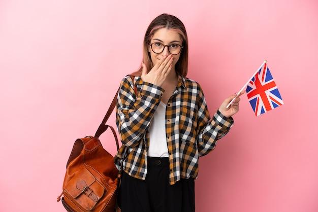 ピンクの壁に分離されたイギリスの旗を持って幸せで笑顔の若いヒスパニック系の女性が手で口を覆っている