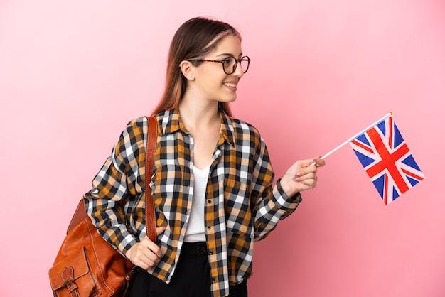 ピンクの壁の側面に分離されたイギリスの旗を保持している若いヒスパニック系女性