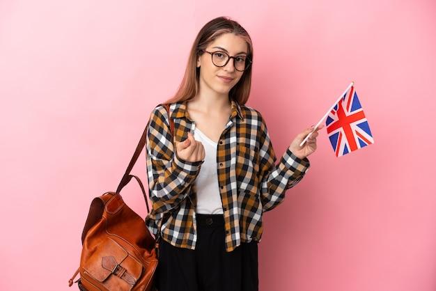 ピンクの壁に分離されたイギリスの旗を持ってお金を稼ぐジェスチャーを保持している若いヒスパニック系女性