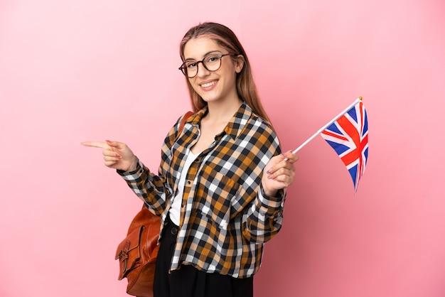 横に指を指しているピンクの壁に分離されたイギリスの旗を保持している若いヒスパニック系女性