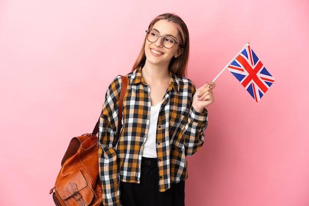 見上げながらアイデアを考えてピンクの壁に分離されたイギリスの旗を保持している若いヒスパニック系女性