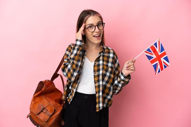 驚きとショックを受けた表情でピンクの壁に分離されたイギリスの旗を保持している若いヒスパニック系女性