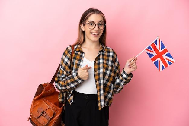 驚きの表情でピンクに分離されたイギリスの旗を保持している若いヒスパニック系女性