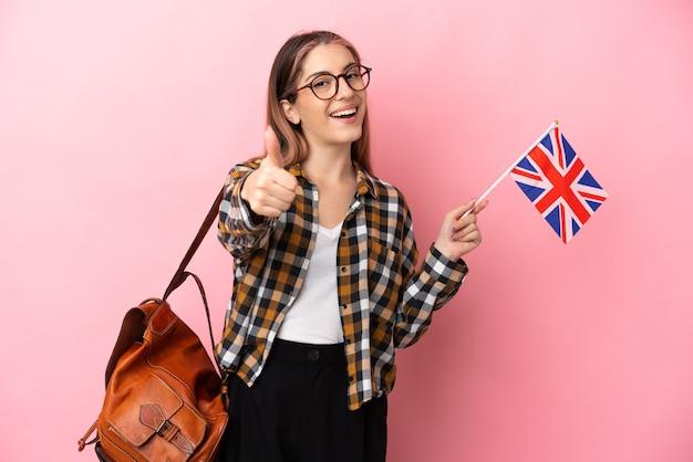 何か良いことが起こったので、親指を立ててピンクで隔離されたイギリスの旗を保持している若いヒスパニック系女性