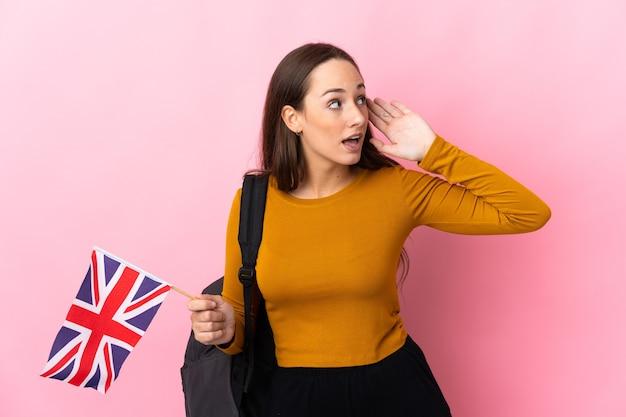 귀에 손을 넣어 뭔가를 듣고 영국 국기를 들고 젊은 히스패닉 여자