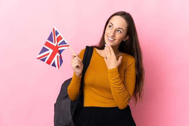 웃는 동안 찾고 영국 국기를 들고 젊은 히스패닉 여자
