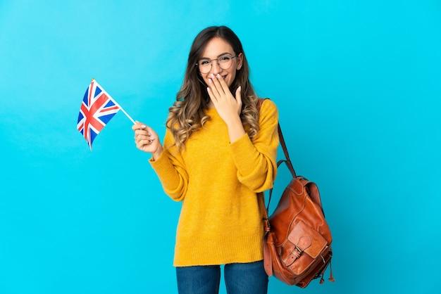 파란색 행복에 영국 국기를 들고 젊은 히스패닉 여자 손으로 입을 덮고 웃고