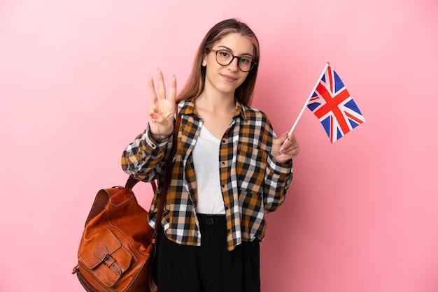 ピンクの幸せなイギリスの旗を保持し、指で3を数える若いヒスパニック系女性