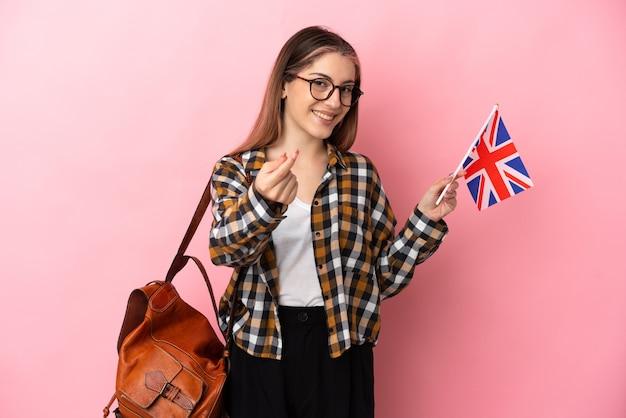 ピンクのお金を稼ぐジェスチャーでイギリスの旗を保持している若いヒスパニック系女性