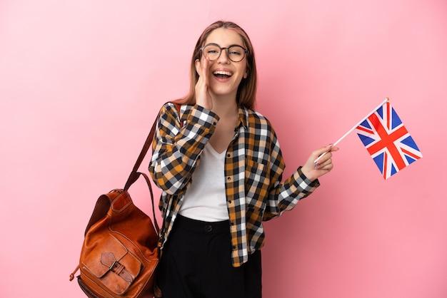 口を大きく開いてピンクの叫びにイギリスの旗を保持している若いヒスパニック系女性