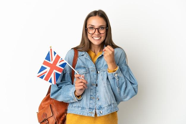 勝者の位置での勝利を祝う孤立した白い背景の上にイギリスの旗を保持している若いヒスパニック系女性