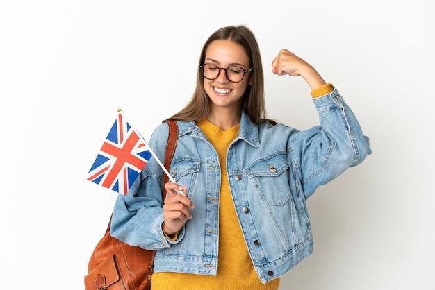 Молодая латиноамериканская женщина, держащая флаг соединенного королевства на изолированном белом фоне, делает сильный жест