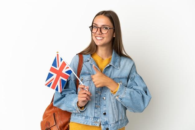 제스처를 엄지 손가락을주는 고립 된 흰색 배경 위에 영국 국기를 들고 젊은 히스패닉 여자