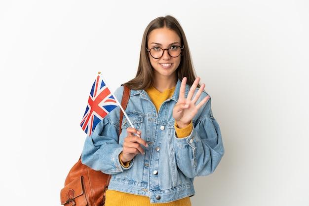 幸せな孤立した白い背景の上にイギリスの旗を保持し、指で4を数える若いヒスパニック系女性