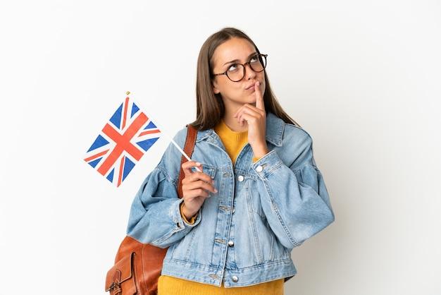 찾는 동안 의심을 갖는 고립 된 흰색 배경 위에 영국 국기를 들고 젊은 히스패닉 여자