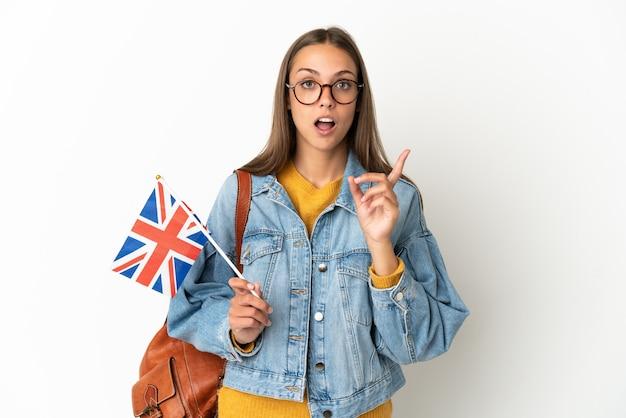 Молодая латиноамериканская женщина держит флаг соединенного королевства на изолированном белом фоне, намереваясь реализовать решение, подняв палец вверх