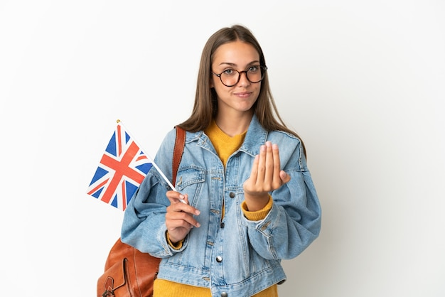 手で来るように誘う孤立した白い背景の上にイギリスの旗を保持している若いヒスパニック系女性。あなたが来て幸せ