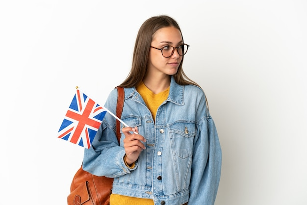 측면을 찾고 격리 된 흰색 배경 위에 영국 국기를 들고 젊은 히스패닉 여자