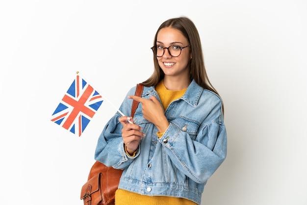 Молодая латиноамериканская женщина держит флаг соединенного королевства на изолированном белом фоне, указывая пальцем в сторону