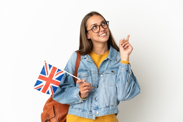 素晴らしいアイデアを指している孤立した白い背景の上にイギリスの旗を保持している若いヒスパニック系女性
