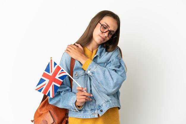 Молодая латиноамериканская женщина, держащая флаг соединенного королевства на изолированном белом фоне, страдает от боли в плече за то, что приложила усилия