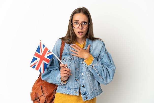 孤立した白い背景の上にイギリスの旗を持っている若いヒスパニック系女性は、右を見ながら驚いてショックを受けました