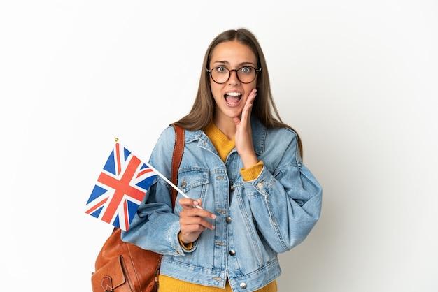 놀라움과 충격 된 표정으로 격리 된 흰색 배경 위에 영국 국기를 들고 젊은 히스패닉 여자