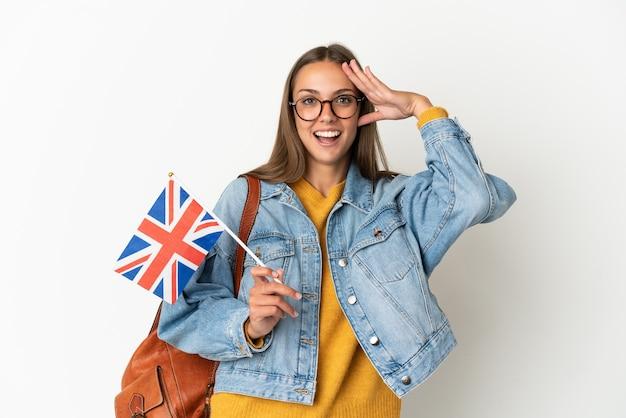 놀라운 표정으로 격리 된 흰색 배경 위에 영국 국기를 들고 젊은 히스패닉 여자