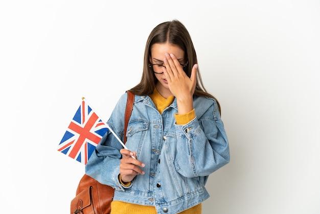 피곤하고 아픈 표정으로 격리 된 흰색 배경 위에 영국 국기를 들고 젊은 히스패닉 여자