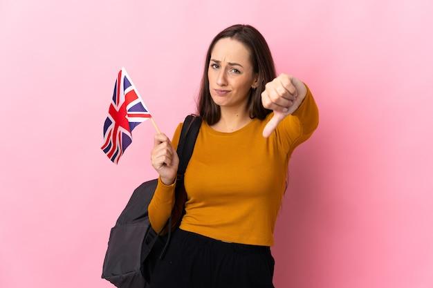 Молодая латиноамериканская женщина, держащая флаг соединенного королевства, показывает большой палец вниз с отрицательным выражением лица