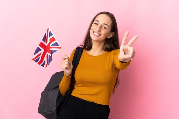 笑顔で勝利のサインを示すイギリスの旗を保持している若いヒスパニック系女性