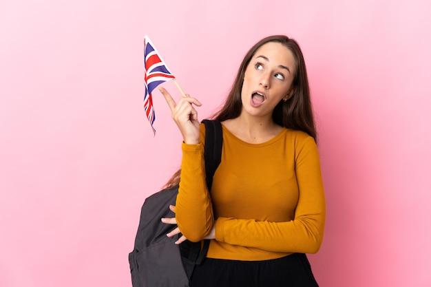 Молодая латиноамериканская женщина, держащая флаг соединенного королевства, думает, что идея указывает пальцем вверх