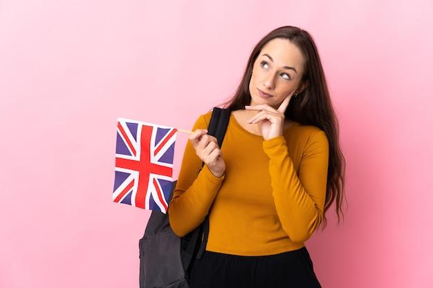 Молодая латиноамериканская женщина, держащая флаг соединенного королевства, думает о идее, глядя вверх