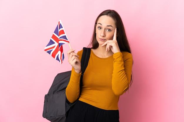 Молодая латиноамериканская женщина, держащая флаг соединенного королевства, думает об идее