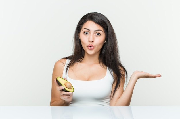 Young hispanic woman holding an avocado impressed holding  on palm.
