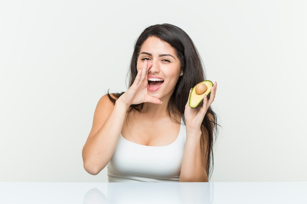 Young hispanic woman holding an avocado shouting excited to front.