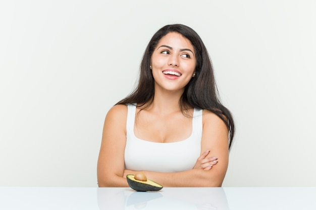 Young hispanic woman holding an avocado smiling confident with crossed arms.