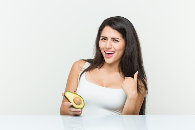 Young hispanic woman holding an avocado surprised pointing at himself, smiling broadly.