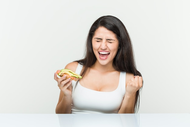 Young hispanic woman holding an avocado toast cheering carefree and excited. victory concept.