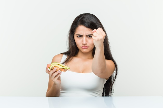 Young hispanic woman holding an avocado toast showing fist to camera, aggressive facial expression.