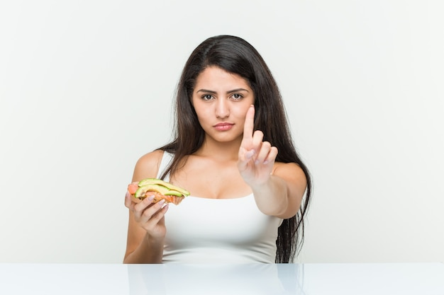 Young hispanic woman holding an avocado toast showing number one with finger.