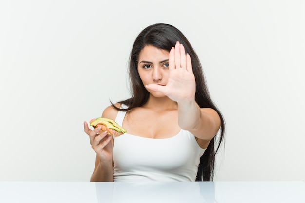 Young hispanic woman holding an avocado toast standing with outstretched hand showing stop sign, preventing you.