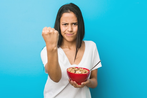 Young hispanic woman holding a cereal bowl showing fist to camera, aggressive facial expression.