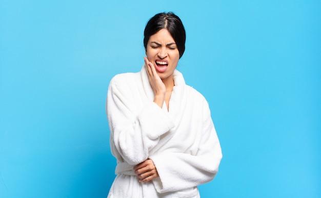 頬を抱え、痛みを伴う歯痛に苦しんでいる若いヒスパニック系女性は、歯科医を探して、気分が悪く、惨めで不幸です。バスローブのコンセプト