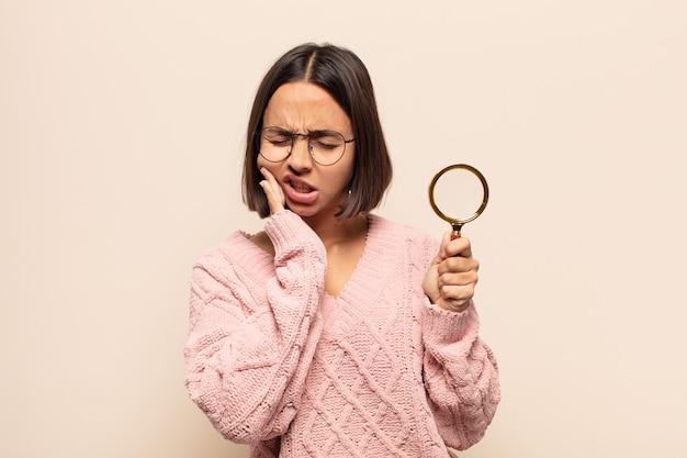 頬を抱え、痛みを伴う歯痛に苦しんでいる若いヒスパニック系女性、気分が悪く、惨めで不幸で、歯科医を探しています
