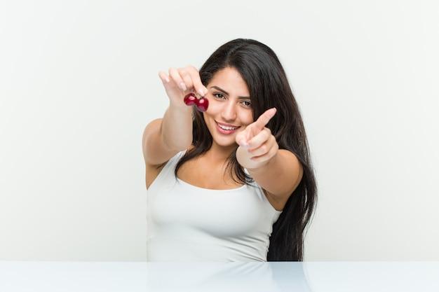 Молодая испанская женщина, держащая вишни веселые улыбки, указывая на фронт.