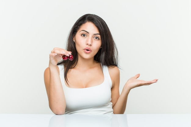 Young hispanic woman holding cherries impressed holding copy space on palm.