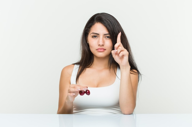 Young hispanic woman holding cherries showing number one with finger.