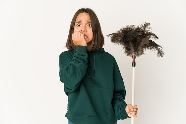 Young hispanic woman holding a duster biting fingernails, nervous and very anxious.
